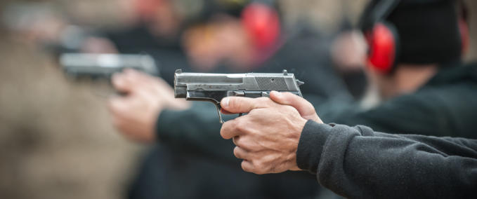 Close-up view of shooter practice handgun shooting in row group